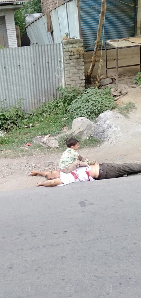 This 3 year old holding blood stained biscuits in his hands sits on his dead grandfather's chest in an attempt to wake him up.  The man was on his way to buy milk for his grandchild but Indian forces pulled him out of his car and shot him dead in Sopore, Kashmir.<br>http://pic.twitter.com/oa1j0xERNF