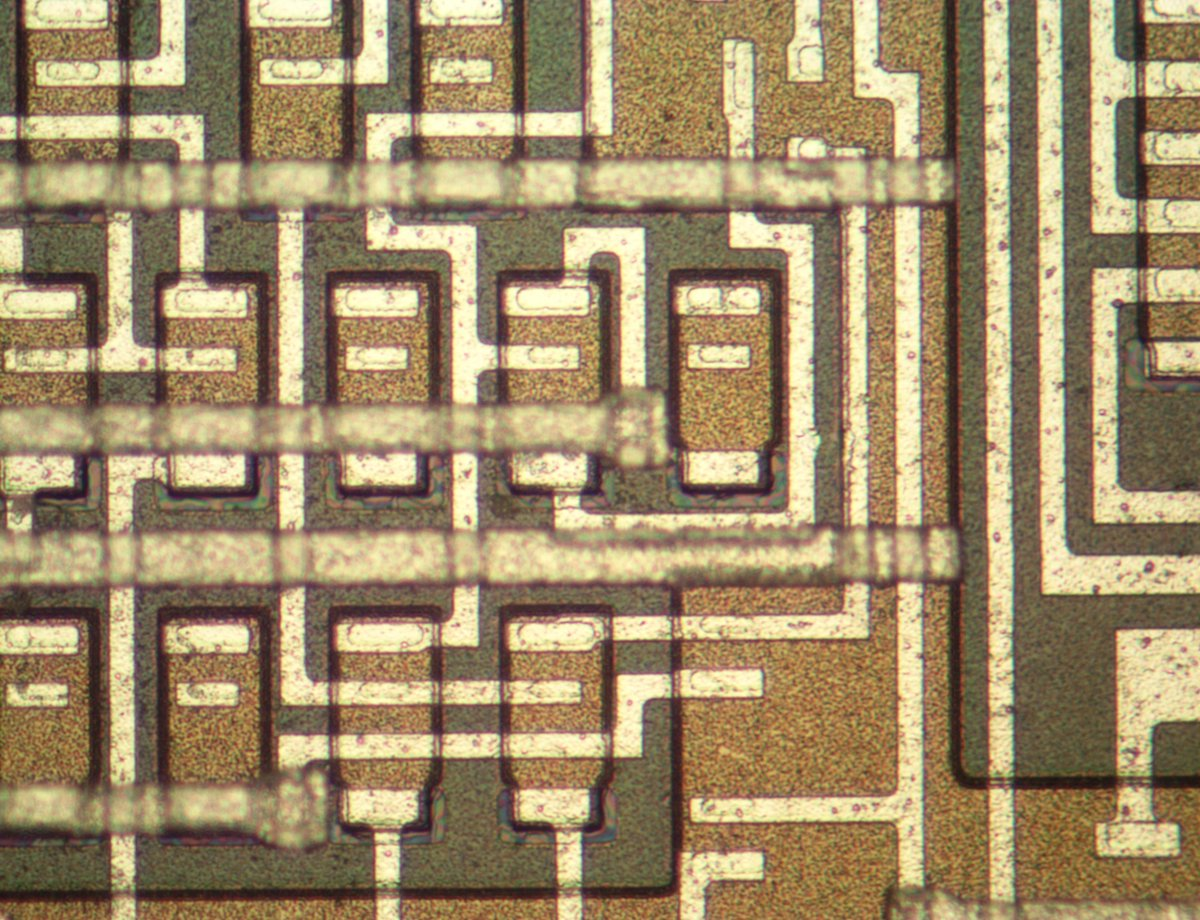 A closeup of the die, showing about a dozen transistors: brownish rectangles with three metal connections. The lower metal layer is connected to the transistors, while a thicker metal layer on top providing interconnections.