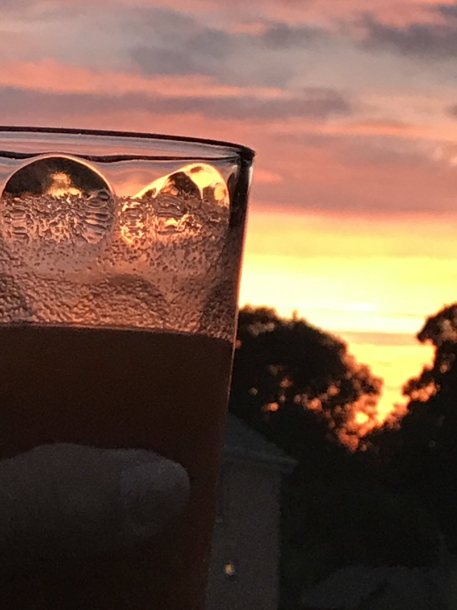 Tonight's sunset is about as orange as my Metamucil. (That's Angie's thumb on the glass)