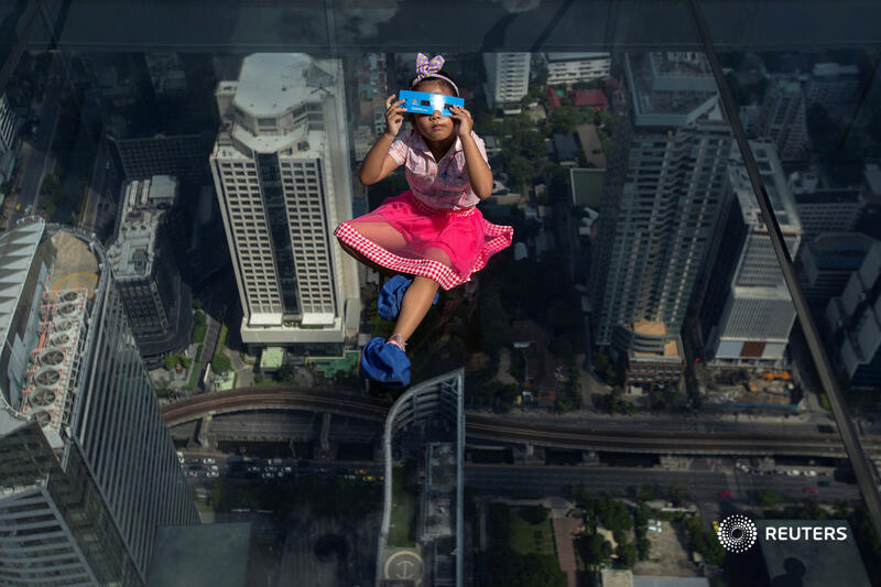 A girl observes a partial solar eclipse while sitting on a glass skywalk in Bangkok, Thailand. More photos of the day: https://t.co/AXBSMlcEnf 📷 @Athit_P https://t.co/hFSD9rYffV