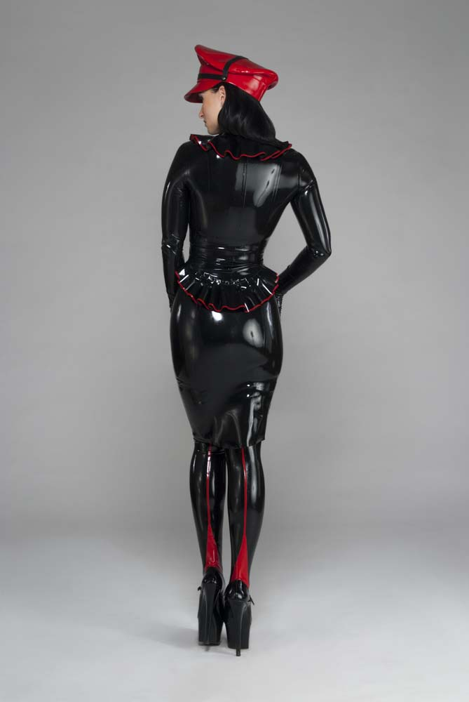 Woman in black latex skirt, top, and leggings, with a red rubber cap.
