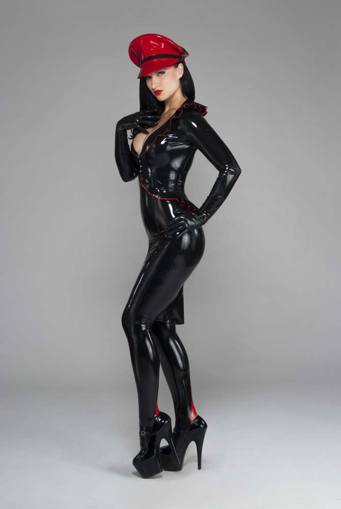 Seen from the side, a model is wearing form-fitting latex from head to toe with a red Muir cap on top.