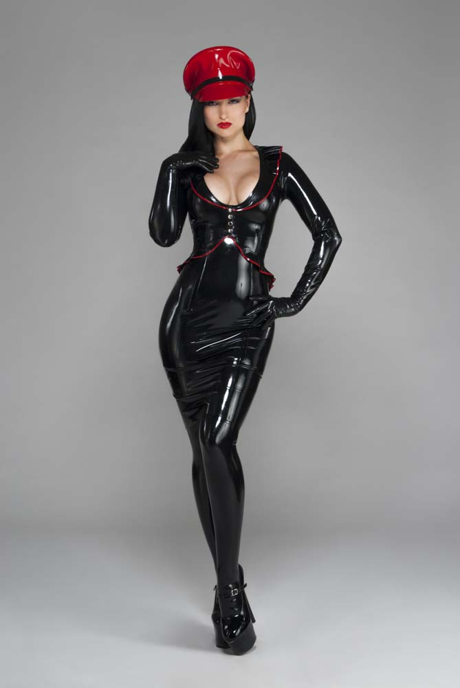 A dominant-looking woman faces the camera in a low-cut latex top, black latex leggings, and a red rubber Muir cap.