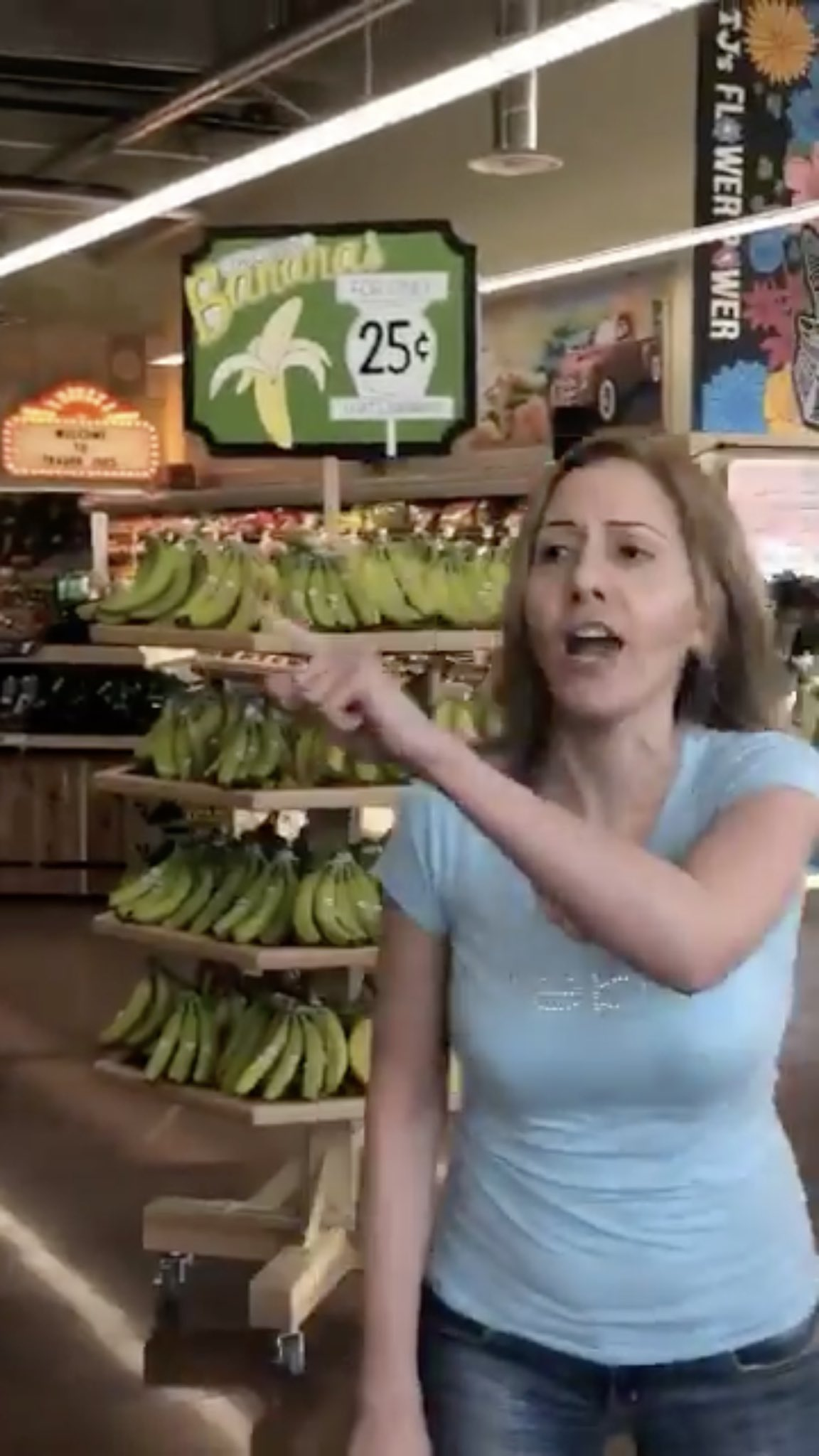 Trader Joe's Karen standing next to banana sign