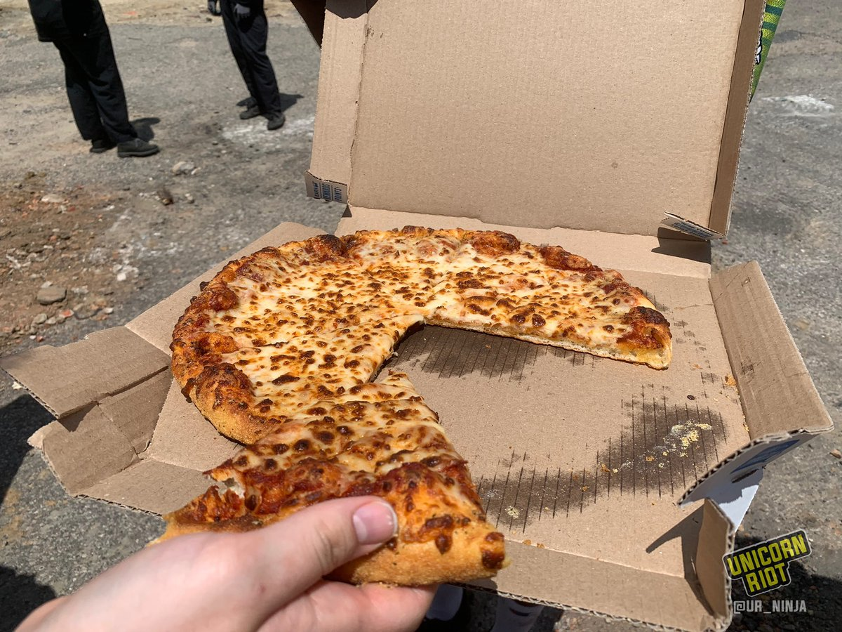 Pizza is getting handed out now after someone ordered several large pies delivered to the encampment
