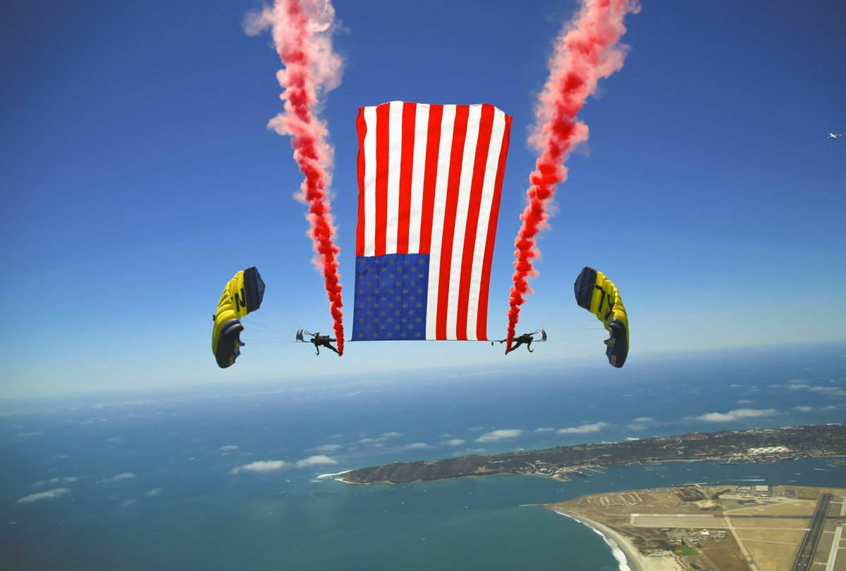 In it together! Members of the @NavyLeapFrogs perform a tethered flag with smoke brackets over San Diego.