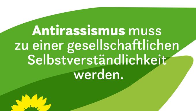 """Auf grünen Blütenblättern steht: """"Antirassismus muss zu einer gesellschaftlichen Selbstverständlichkeit werden."""""""