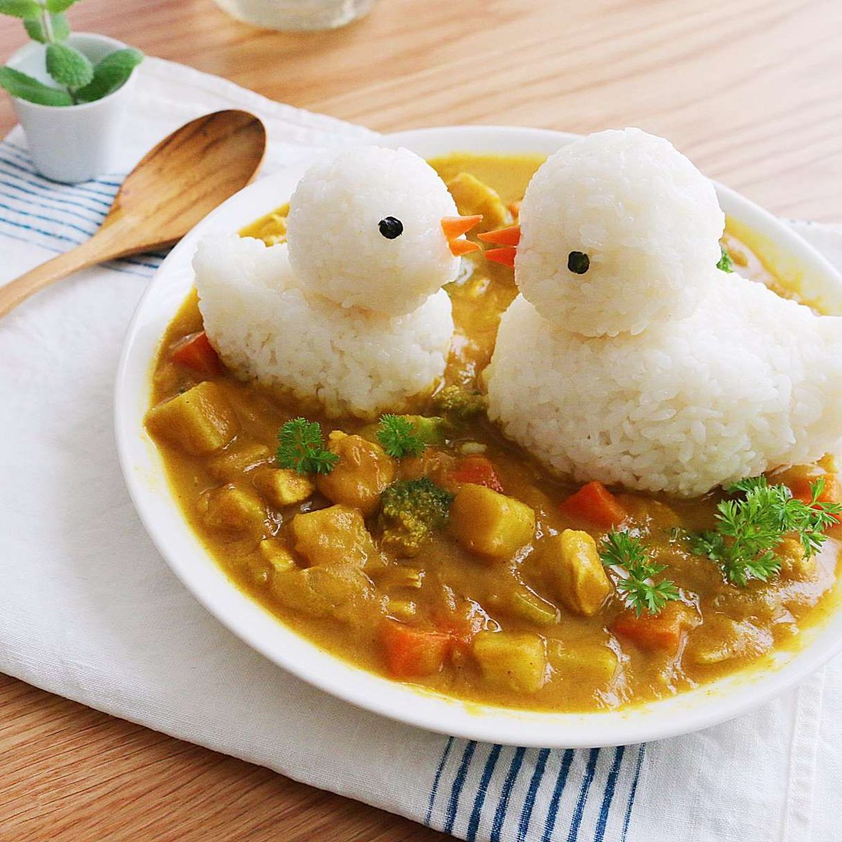 oh to be ducks made from rice sitting on a plate of curry