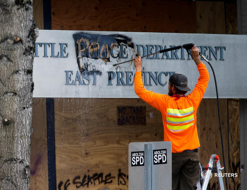 A worker cleans off the word 'people' graffitied over the word 'police' at the Seattle Police Department's East Precinct as they retake the Capitol Hill CHOP area. More top photos of the week: https://t.co/pTJKDsMfdz 📷 @lindseywasson https://t.co/1YVg7iSCpG