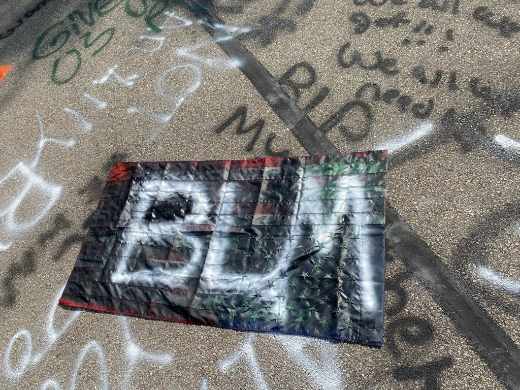 """You can wash our art and chalk off the streets but you must also address the markings that stain our American flag. The words """"Black Lives Matter"""" written over red conformity, white purity and blue authority. Painted by the people you claim to """"serve"""" but kill, starve and neglect https://t.co/36bUm06r8t"""