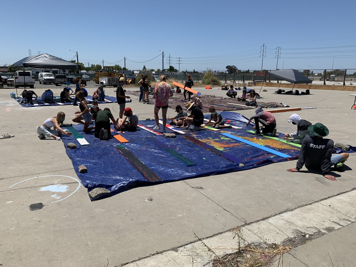 "Day 3: @CampKeeTov campers painting ""prayer & blessing murals"" on fence planks and painting planter planks for our Tiny House Village at the site, 633 Hegenberger in Oakland.  #Day3 #campers #youth #staff #painting #prayers #blessings #murals #fenceplanks #planterplanks https://t.co/MHorTkaIgk"