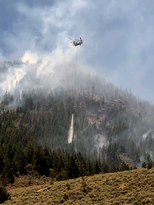 A helicopter drops water on a forested mountainside as smoke rises from a wildfire.