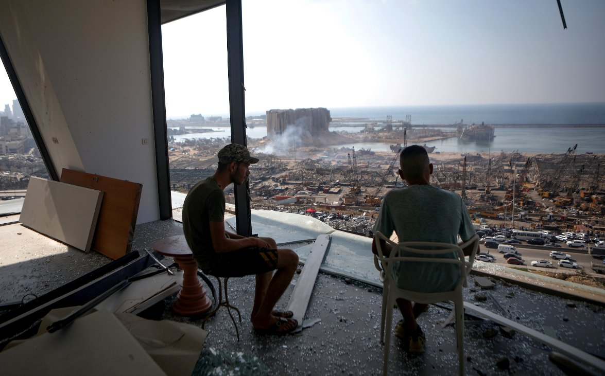 PHOTO: Two men gaze at the devastated Beirut port from a damaged building in the nearby neighbourhood of Mar Mikaehl, two days after a massive blast shook the Lebanese capital. The blast killed at least 137 people, left dozens missing and at least 5,000 wounded. #NTVNews    AFP pic.twitter.com/rPPTP31RsV