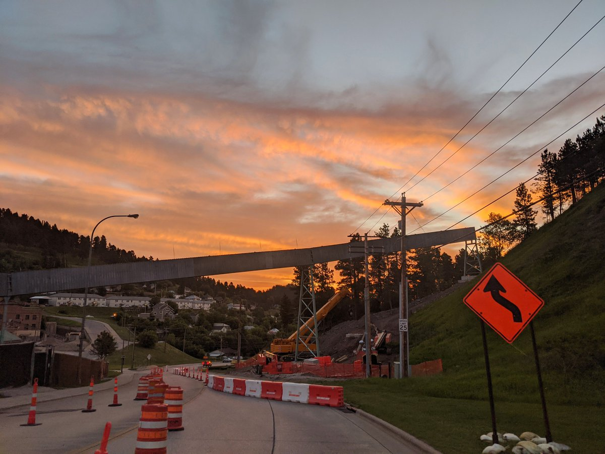 The conveyor system for the Long Baseline Neutrino Facility is being constructed over Highway 85 in Lead. Jamey Tollefson took this photo to mark the crews' progress and a brilliant sunrise on July 23. #PhotoOfTheWeek pic.twitter.com/9r9agBs1qE