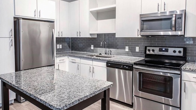 Beautiful! Just another reason to call The Pierpont home. What do you love most about our chef-inspired kitchen: the white cabinetry, sleek stainless appliances, versatile island or modern backsplash? #thepierpont #springtexas #ironchefkitchen