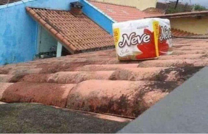 Um telhado com um pacote de papel higiênico neve em cima