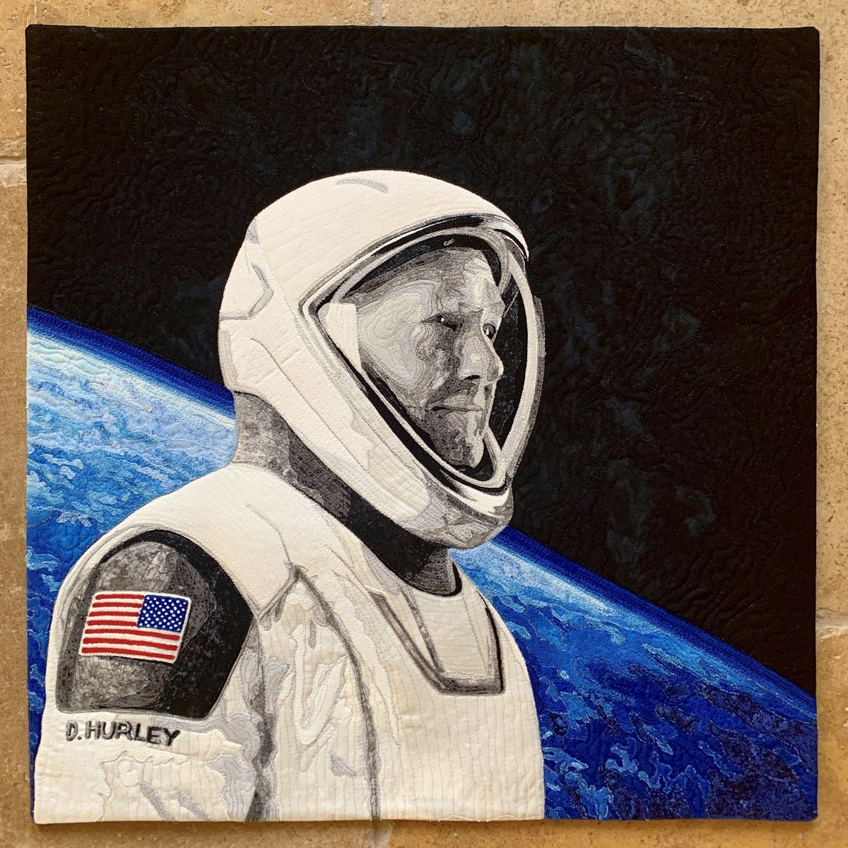 """My latest art quilt is @Astro_Doug's SpaceX crew photo! I used a picture of Earth he took from ISS as inspiration for the background. Our son Jack proposed the idea of making Doug B&W with only the flag on his shoulder colored. Perfect! Medium: fabric & thread, 21.5"""" square. https://t.co/G2OOJ1KB6q"""