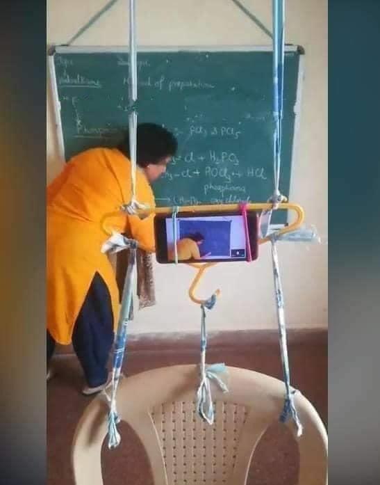 Maestra escribiendo en la pizarra mientras ésta conduce una video conferencia.