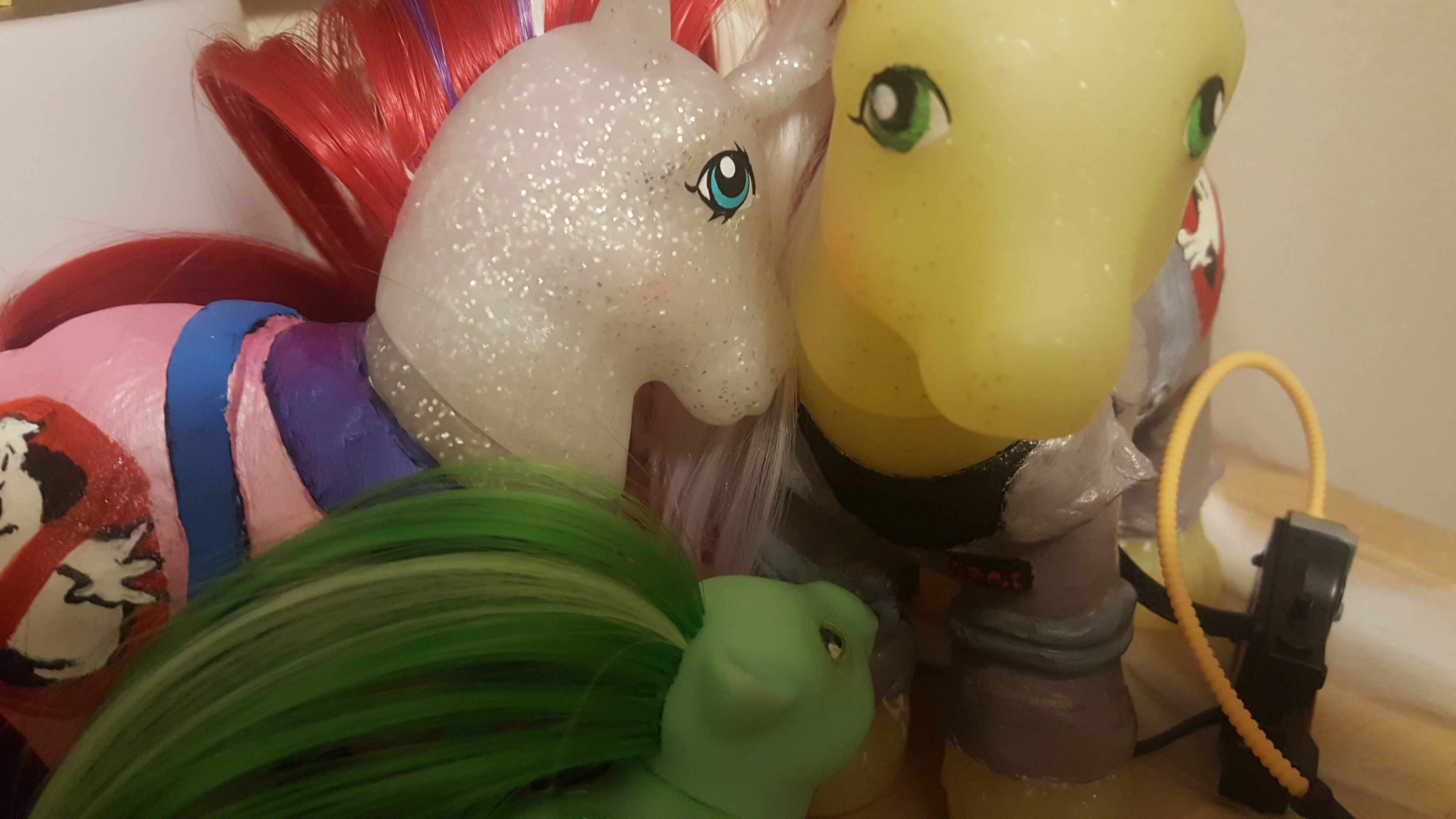 Janine (white glitter unicorn with blue eyes, red hair and a pink and purple Ghostbusters jumpsuit) nuzzles Egon (yellow glitter pony with green eyes, white hair and a tan Ghostbusters jumpsuit) while Slimer looks up at them (green baby pony with green hair)