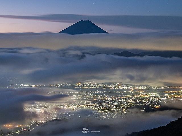 【絶景】11日早朝、山梨・甲府盆地周辺で雲海が発生山梨・韮崎市で撮影。雲海の一部が街灯りで輝き、その奥には夜が明け始めたグラデーションの空に富士山が頭をのぞかせている。