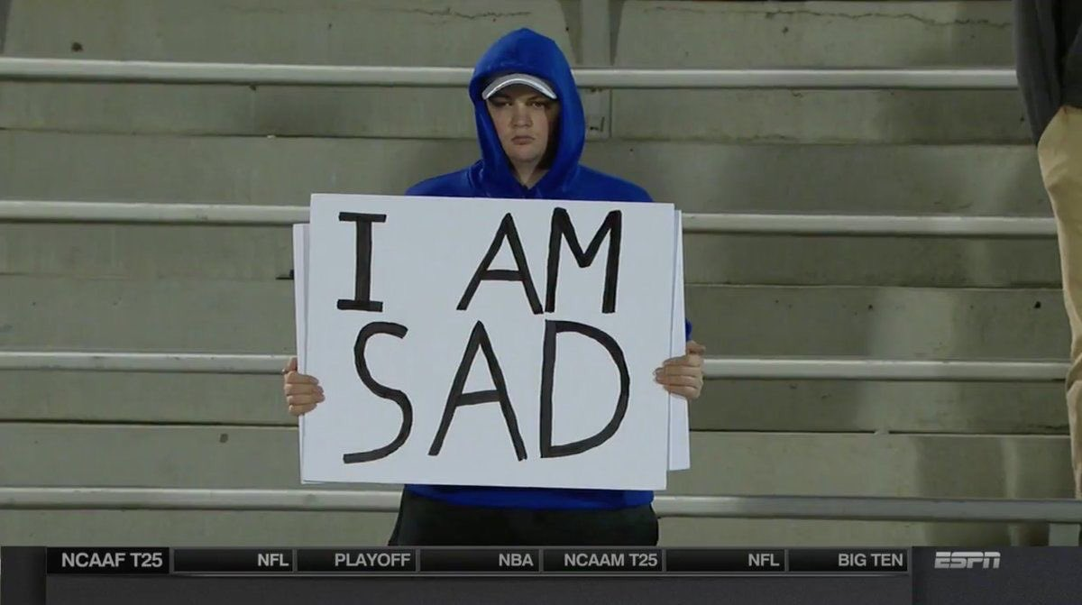 "A football fan standing alone in the stadium holding a sign that reads ""I AM SAD""."