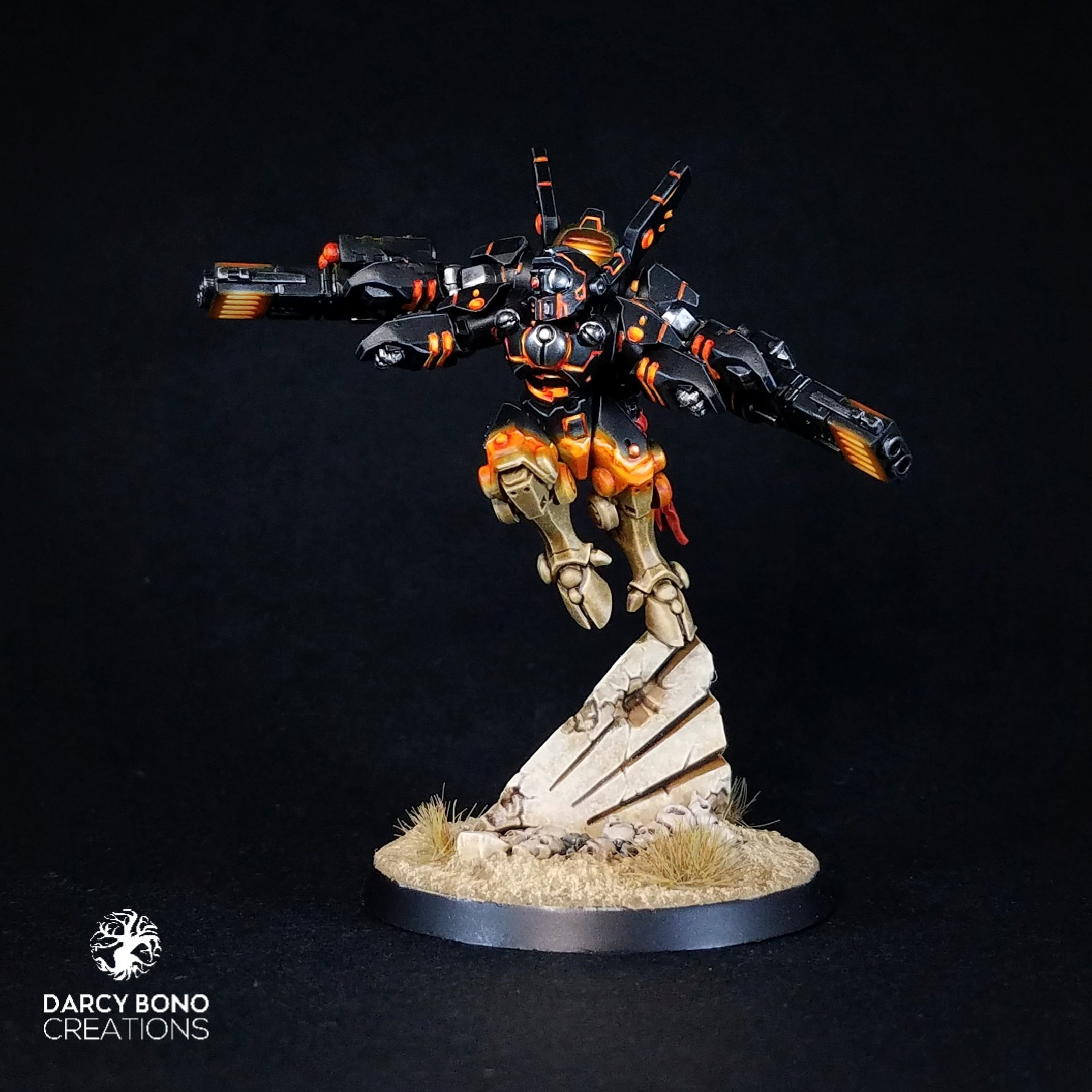 a Games Workshop T'au Commander Shadowsun miniature, painted in a striking black and orange colour scheme with the bottom half camouflaging itself against the environment.