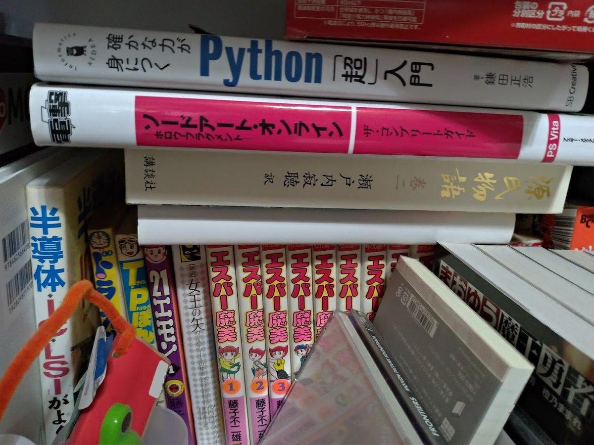 そういや我が家のカオス本棚もう1つ写真あった。藤子不二雄ランドのエスパー魔美と、瀬戸内寂聴の源氏物語の上にSOAの攻略本とPythonの入門書、手前はまおゆうが並ぶ。