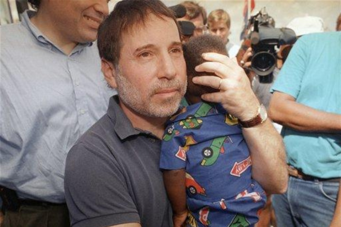 Paul Simon hugs a young boy in Homestead, Florida after Hurricane Andrew on this date September 17 in 1992. Photo by John Gaps III. #OTD https://t.co/cWgVoH0Mgq