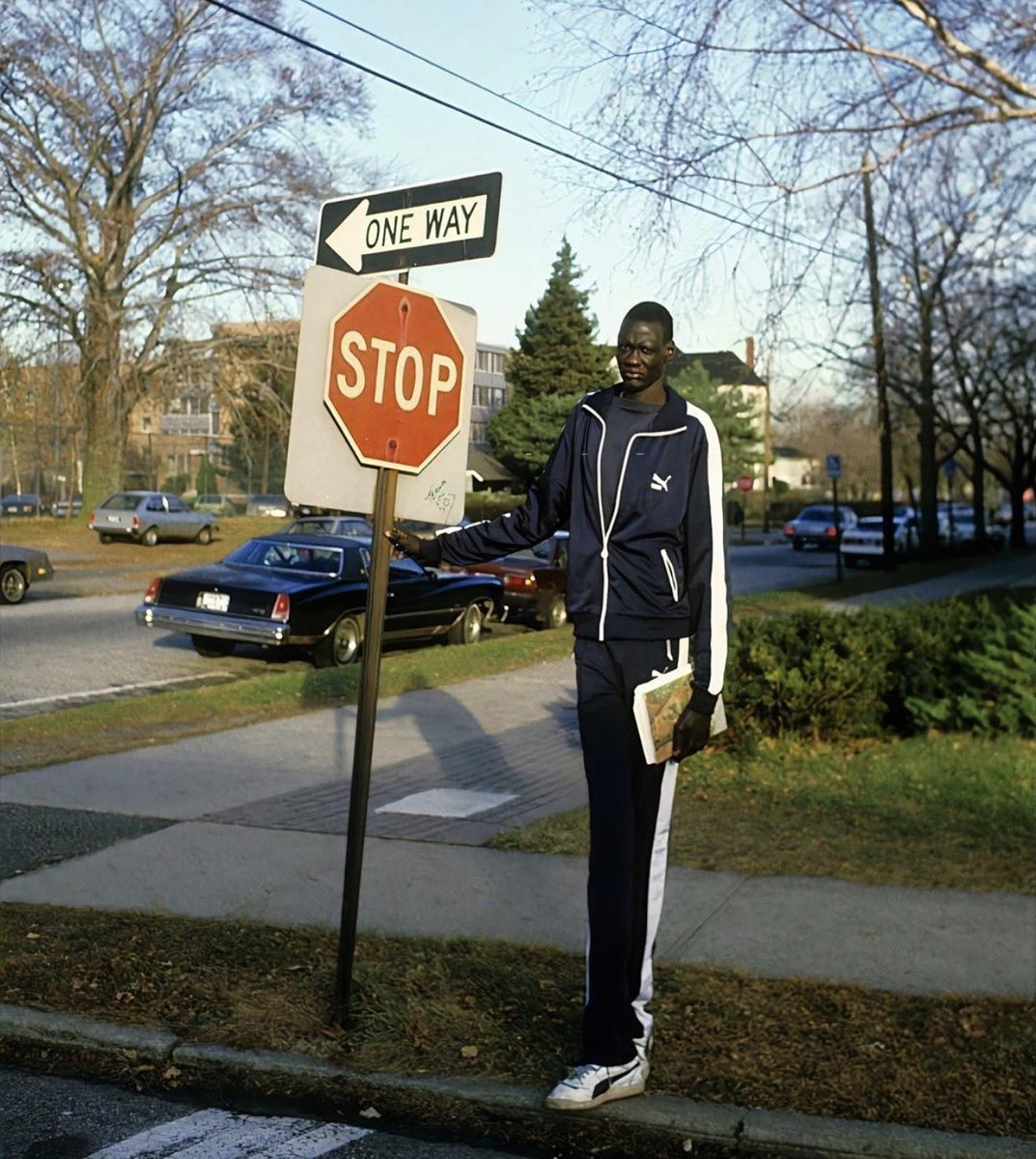 Manute Bol standing next to a stop sign in 1984. 📸