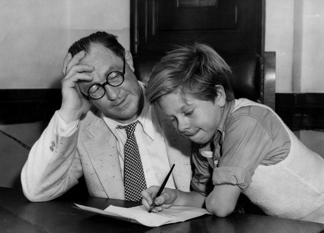 13-year-old actor Mickey Rooney (right) reads his contract and his manager Harry Weber in Los Angeles, California on this date September 18 in 1934. Photo credit: AP. #OTD https://t.co/Wj4NKafO1C