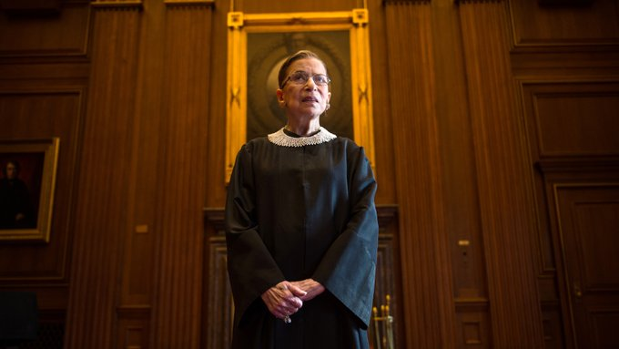 Justice Ruth Bader Ginsburg is shown standing center frame in a judicial robe. She looks beyond the camera and a gold frame is seen on the wall behind her.