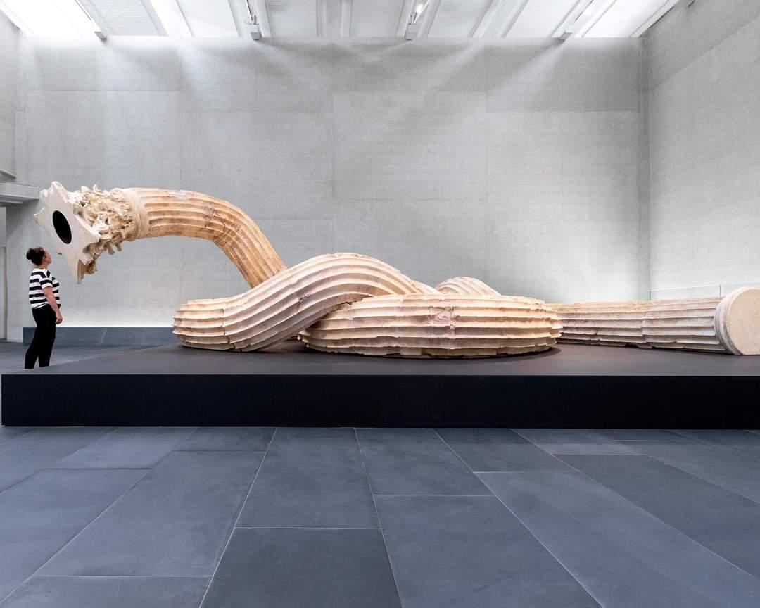 """Oeuvre """" Hello"""" de l'artiste Xu Zhen , ou quand une colonne corinthienne prend vie et lovée, telle un serpent, rencontre une visiteuse...   #art #twitterAntique https://t.co/w49YXpU5VZ"""