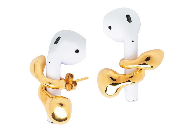 【斬新】「AirPodsを絶対に落とさない」ピアスが登場MISHOのジュエリーデザイナーのアイデア。巻き付いてホールドするゴールドのループを、耳につけるスタイルとなっている。