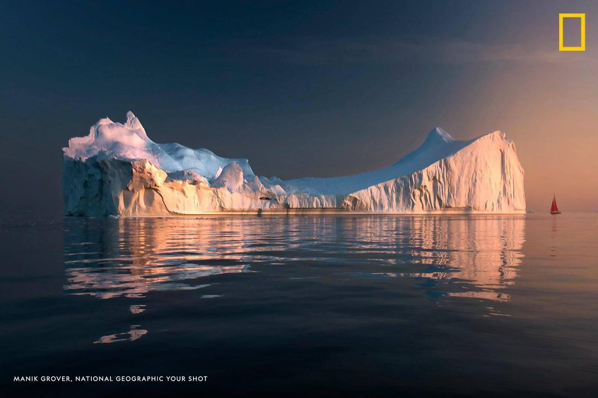 An iceberg dwarfs a passing sailboat in this powerful image captured by Your Shot photographer Manik Grover https://t.co/kGKnPB5QIf
