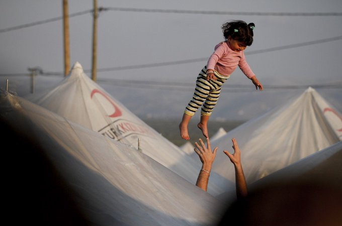 A parent throws their daughter into the air inside a Syrian refugee camp, southern Turkey, by Tara Todras-Whitehill, photojournalist based in Istanbul #womensart