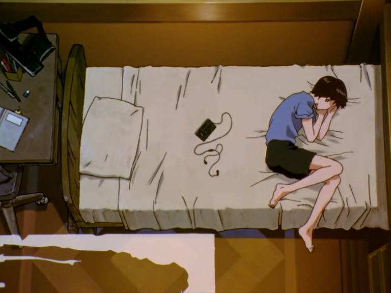 Screencap from Evangelion. Shinji Ikari curled nearly into a fetal position in bed, not using his pillow or his headphones.