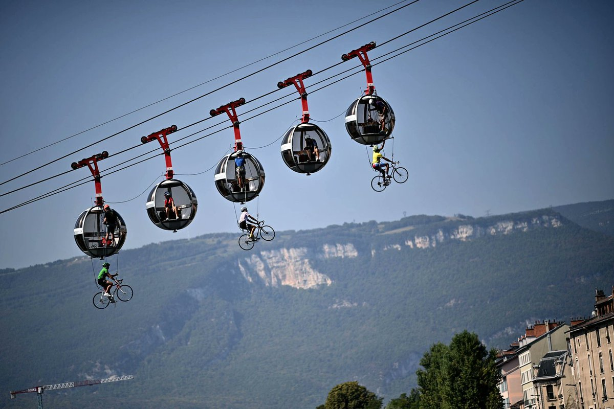 Cyclists hang under the Grenoble Bastille cable cars as competitors pass by during the 17th stage of the Tour de France, between Grenoble and Meribel. Photo: Anne-Christine Poujoulat https://t.co/oHojeJni0V