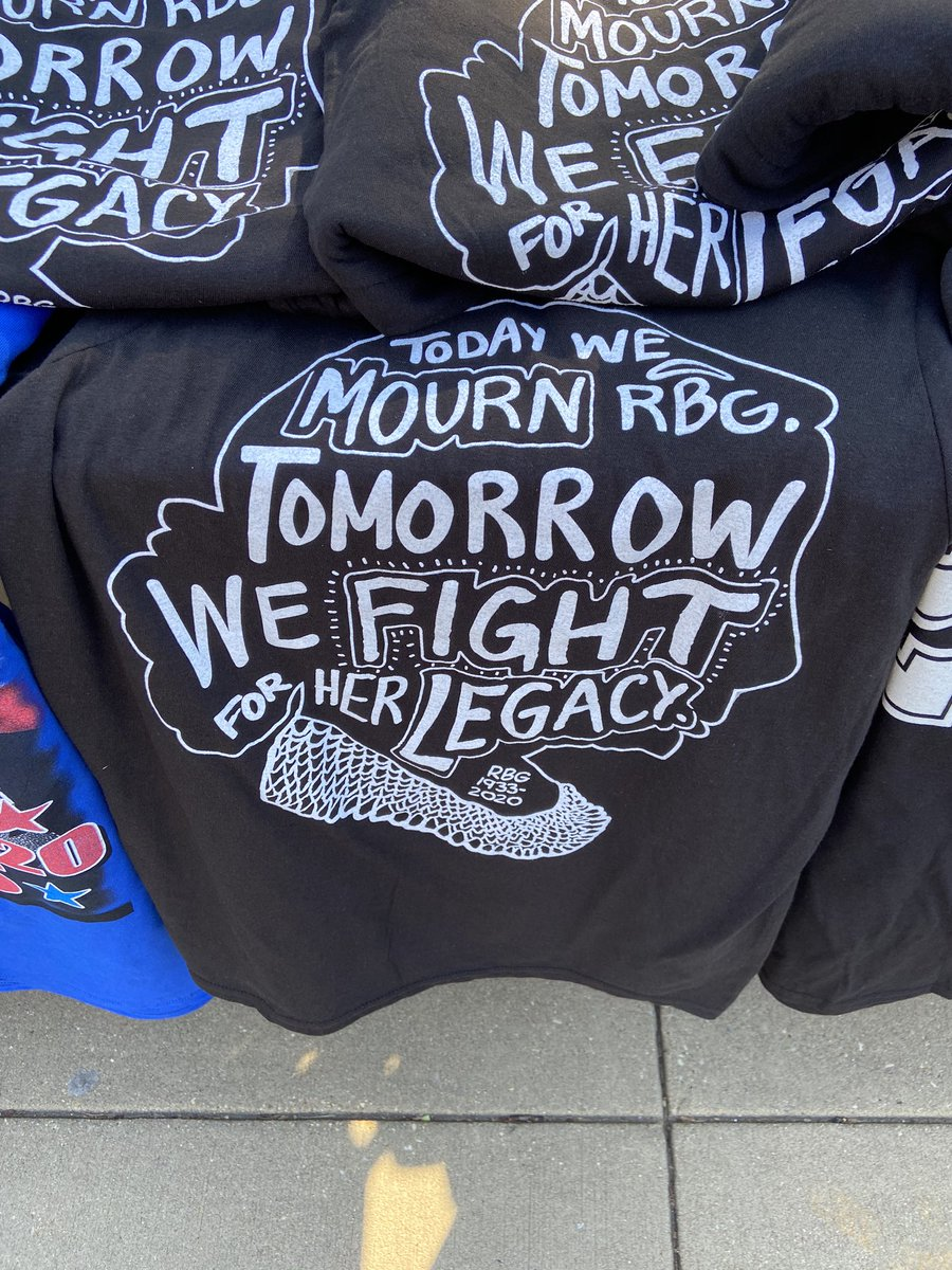 Street vender selling RBG shirts near where people are lining up outside the court