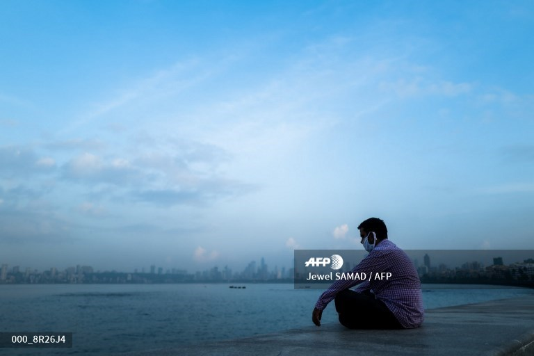 A man wearing a facemask as a preventive measure against the Covid-19 coronavirus rests at the Marine Drive waterfront in Mumbai.  A picture by #AFP photographer @jewelsamad https://t.co/L7NDka5Okg