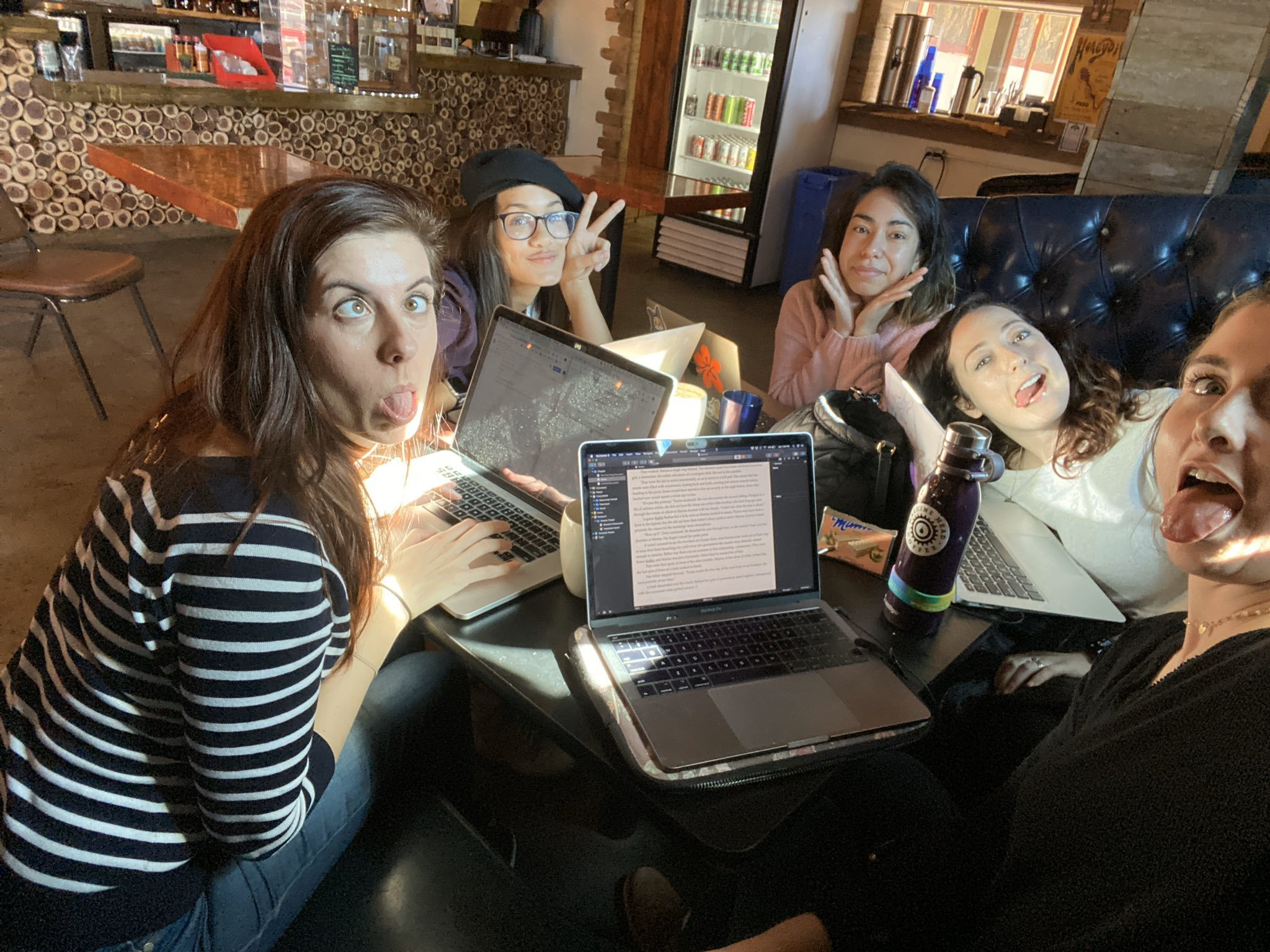 Photo taken pre-COVID of five women at a table in a coffee shop making faces at the camera. Three of the women are sticking out their tongues, the fourth is flashing a peace sign, and the fifth is resting her chin in her hands. Their laptops are in front of them on the table, open to writing projects. They are, left to right: Carol, Brighton, Andy, Melody, and Annemarie.
