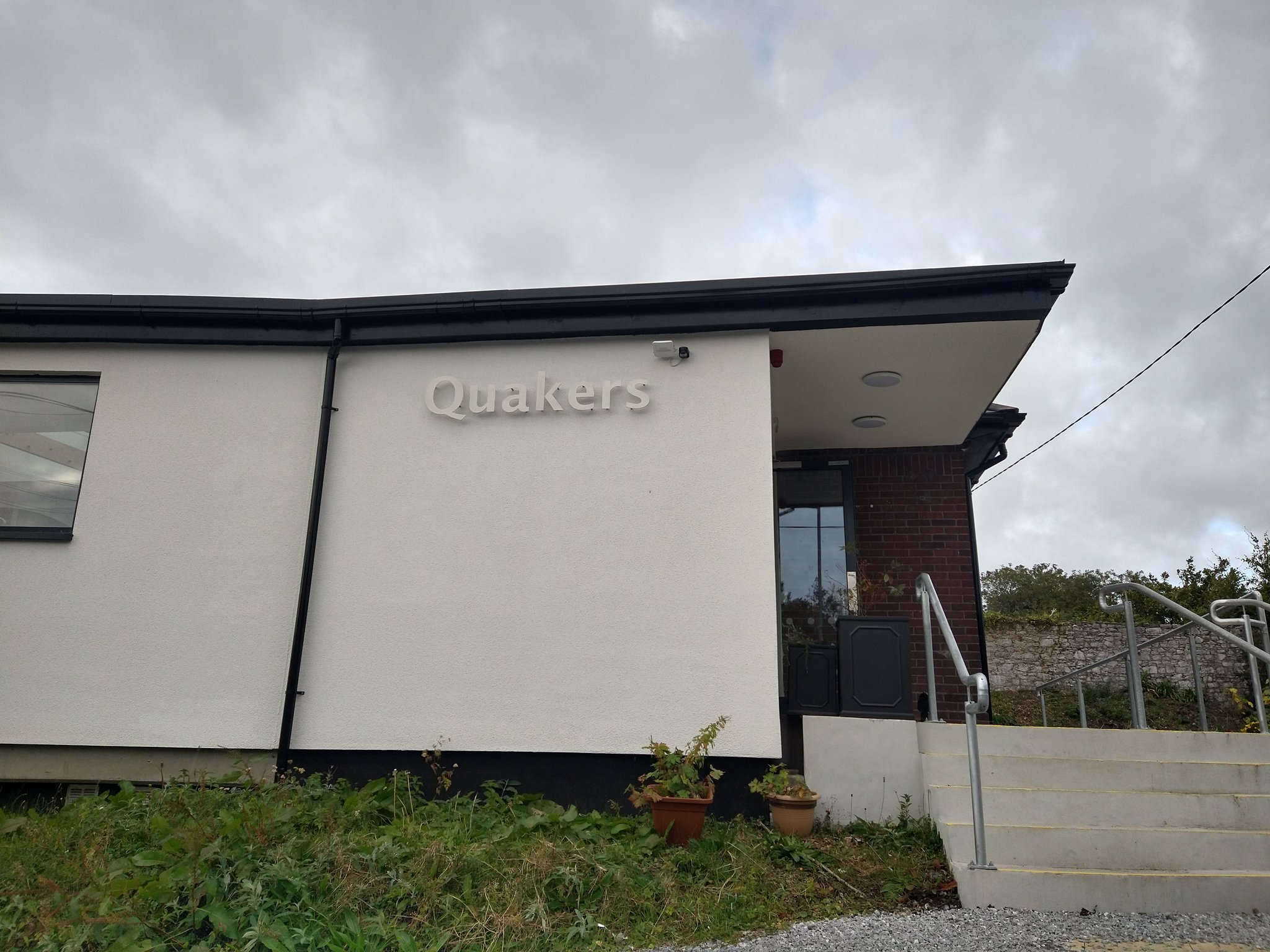 A photo of a light-coloured building with a flat roof. Metallic letters spell out 'Quakers'.
