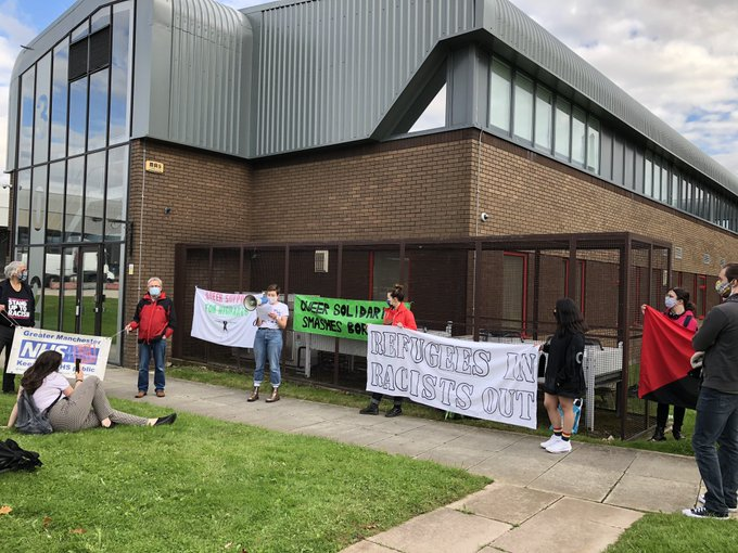 Photo of a protest outside Manchester Short Term Holding facility with signs saying 'Refugees In, Racists Out' and 'Queer Solidarity Smashes Borders' among others