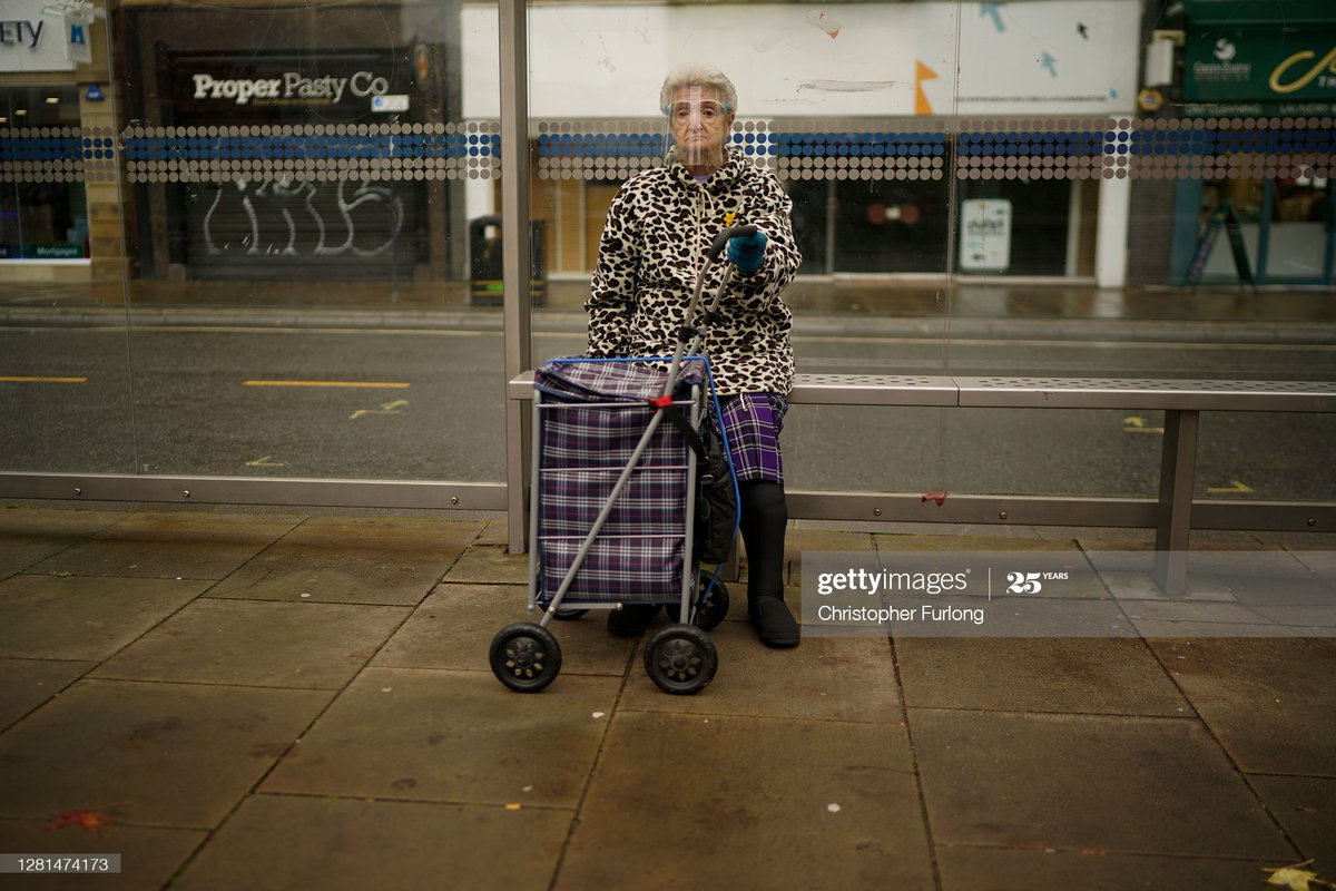 A woman wears a face shield as she sits at a bus stop in Sheffield, England. The county of South Yorkshire, which includes the city of #Sheffield will move to Tier 3 'Very High' #COVID19 alert this weekend. 📷: @Chris_Furlong https://t.co/aUB2yL7OFZ