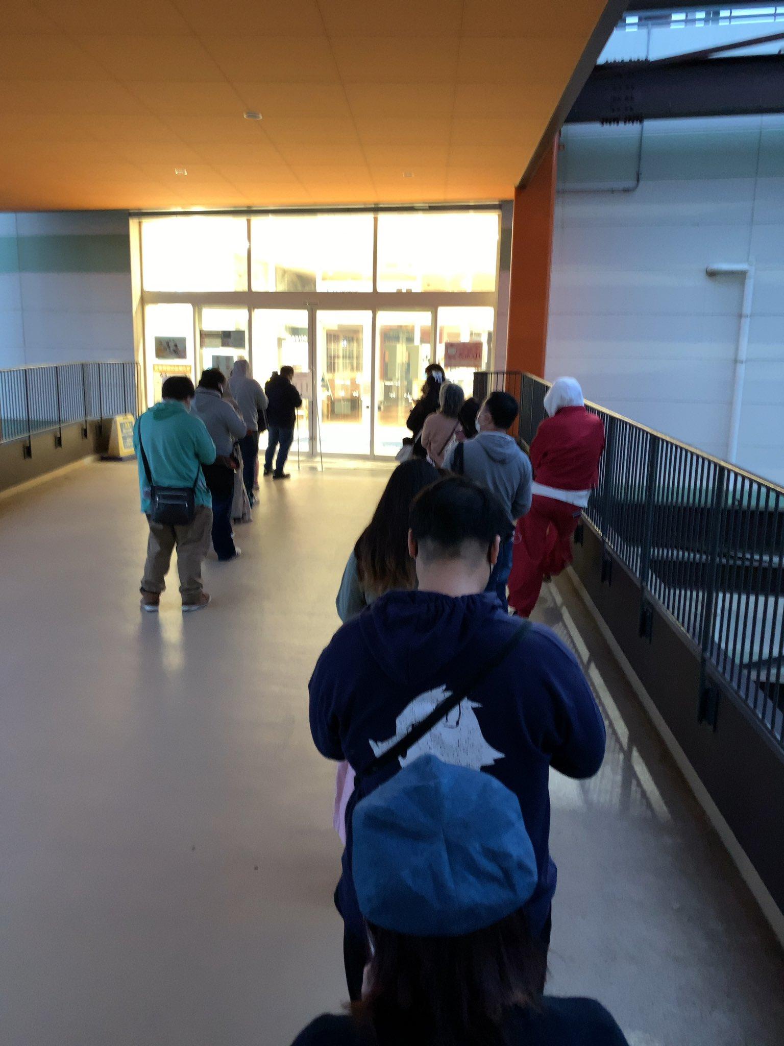 画像,劇場版鬼滅の刃のグッズを買うために列に並んでるところ。平日の朝だし、居ても数人だろ!と思っていたのに、割と居たwパンフのみ購入する列とグッズとパンフを購入する列…