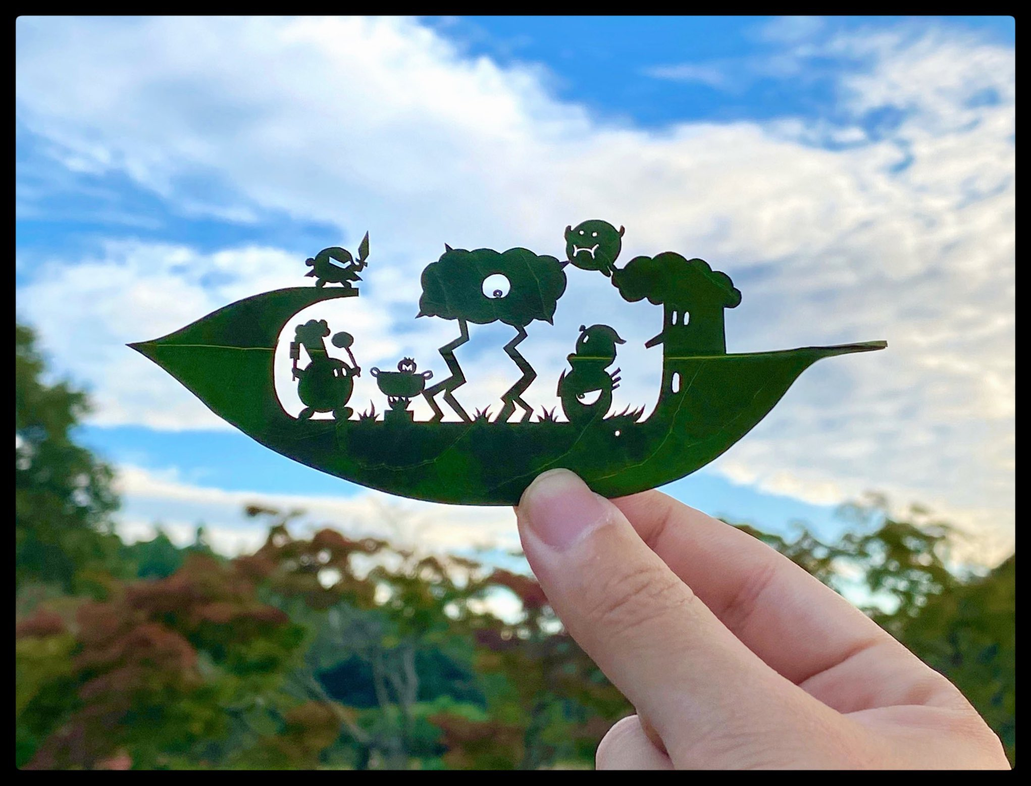 A photo of a hand holding a green leaf that has cut out in it a scene of cartoonish monsters.