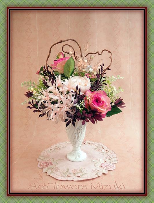 <作品No.180>オーダー品のご紹介です。『久しぶりに再会した先輩へエールをこめて』キウイの蔓はハート型に配し、差し色にエンジ。濃ピンクの薔薇の花言葉は『誇り』そして手前のネリネの花言葉は『また会う日を楽しみに』です。詳細写真をブログにもアップしました〜→