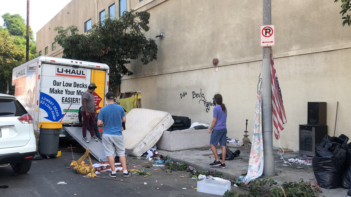 Here at the intersection of Vine/La Miranda where a man who claims to be working for the Hollywood Mental Health Center is loading the belongings of unhoused people into a Uhaul to be dumped.