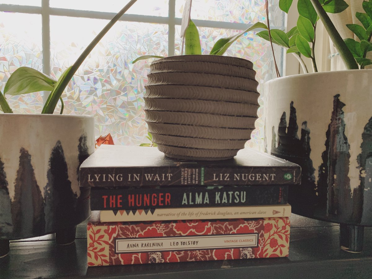 Lying in Wait by Liz Nugent The Hunger by Alma Katzu Narrative of the Life of Frederick Douglass Anna Karenina by Leo Tolstoy  All stacked and pictured surrounded by flowers.