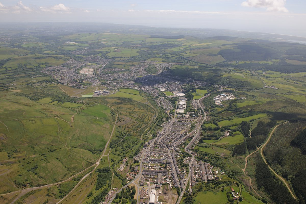 This view looks south down the Llyfni Valley, towards #Nantyffyllon – birthplace of J. J. Williams – with #Maesteg beyond. In the centre of the bottom of the photograph is @NantyffyllonRFC Photo: Toby Driver, @RC_Survey, June 2015 https://t.co/Ur9530fvTW #ExploreYourArchive https://t.co/vjYLmxA82E