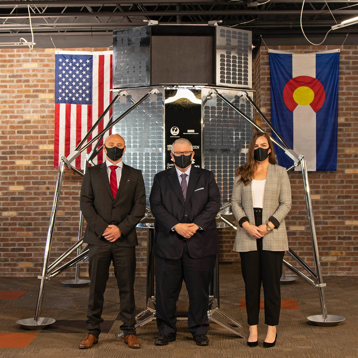 Kevin O'Connell and two others standing in front of a lunar lander with U.S. and Colorado flags in the background